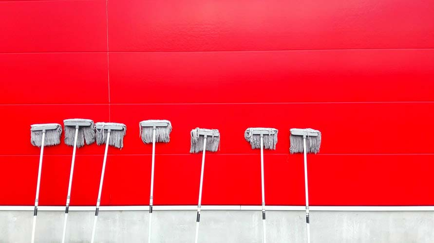 Row of mops on red background
