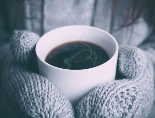 Grey mittened hands holding hot drink