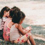 3 children sitting together talking