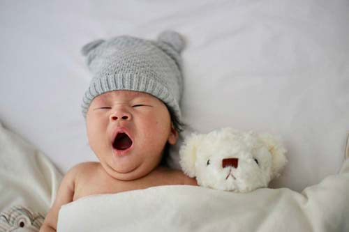 Baby yawning with teddy bear